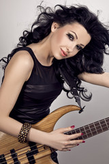A rocker chick plays a wooden bass guitar