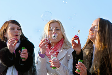 beautiful friends blowing bubbles in the nature