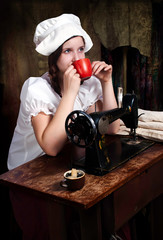 Portrait of a young seamstress with red mug near old sewing mach