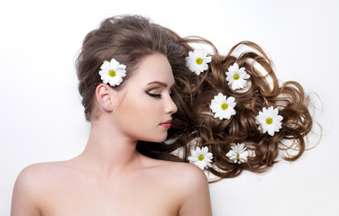 Flowers in long curly hair of woman