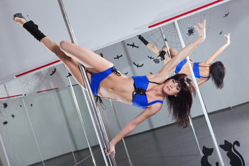 Young woman dancing with pole