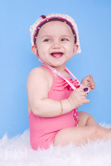 bébé de 8 mois souriante sur fond bleu