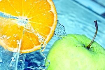 Orange and apple in water splash
