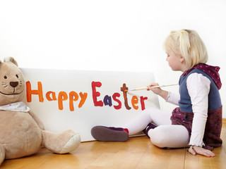 Cute blond girl is painting Happy Easter