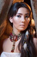 Portrait of American Indian female looking from tent
