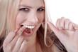 Hübsche blonde Frau reinigt mit Zahnseide ihre Zähne, quer