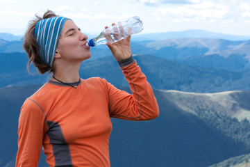 Hiker drinks clear water on top of the mountains