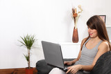Cheerful woman at home on sofa using laptop