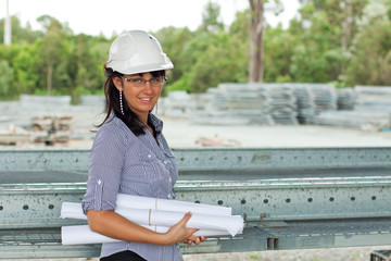 smiling young engineer woman with rolled drawings