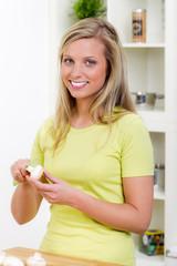 junge hausfrau hält champignon in den händen