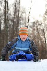 Boy intend drive from hill in winter on sledges