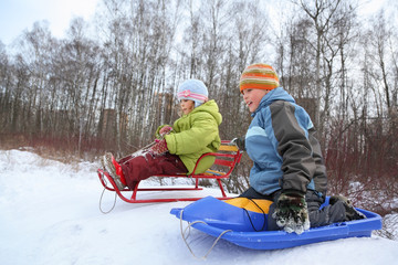 Brother and sister intend  drive from  hill in winter on sledges