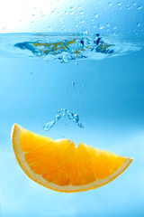 orange slice fruit under water with drops and a splash