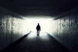 Fototapety Silhouette of Man Walking in Tunnel. Light at End of Tunnel