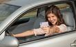 Frau im Auto zeigt Führerschein