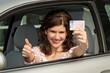 Frau zeigt Topdaumen und Führerschein