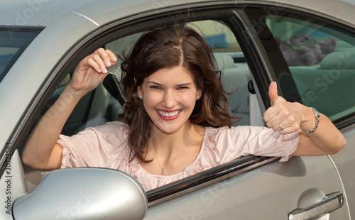 Frau mit Autoschlüssel und Topdaumen
