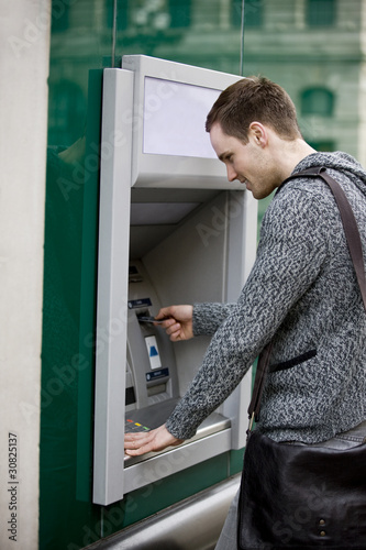 A young man using a cash machine