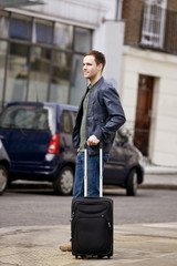 A young man standing in the street, holding his suitcase