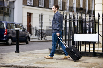 A young man pulling his suitcase in the street