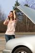 genervte Frau telefoniert nach Autopanne