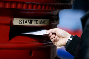 A man posting letters in a letterbox