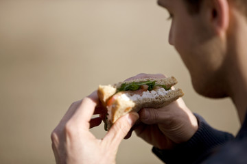 A young man eating a sandwich, close-up