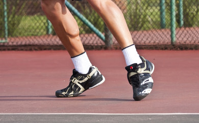 Tennis player legs and feet on court playing