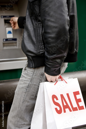 A young man using a cash machine, holding carrier bags