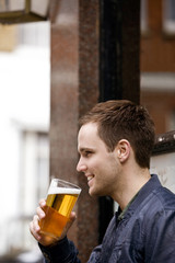 A young man drinking a pint of beer