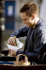 A young man sitting on a bench, eating a sandwich