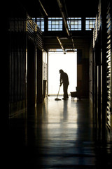 Silhouette of man moping floor