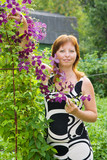woman with clematis in her garden