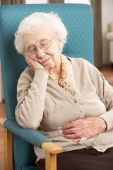 Senior Woman Resting In Chair At Home