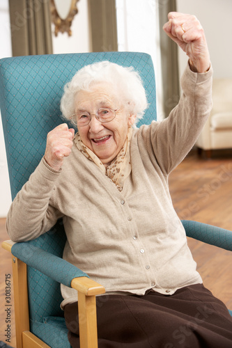 Leinwandbild Motiv Senior Woman Celebrating In Chair At Home