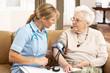 Senior Woman Ihaving Blood Pressure Taken By Health Visitor At H