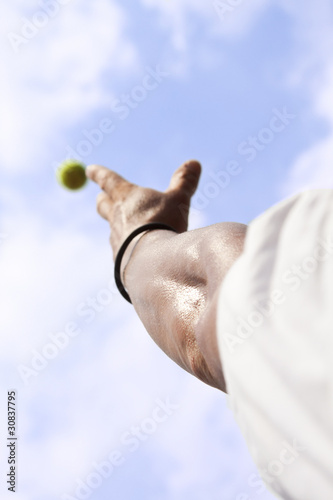 Tennisplayer trowing up a ball with his hand to serve blue sky