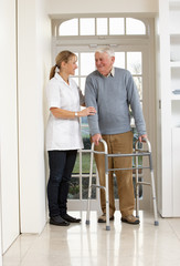 Carer Helping Elderly Senior Man Using Walking Frame