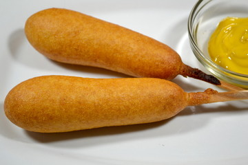 Two Corndogs with Yellow Mustard