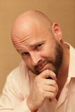 Bald man rubbing his chin poster