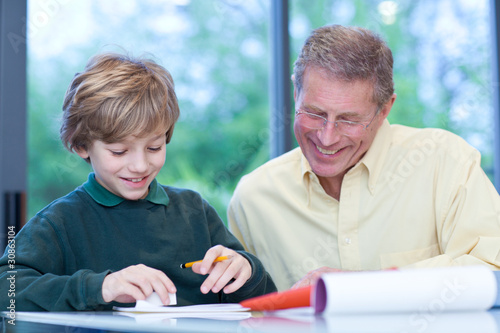 Grandfather watching grandson doing his homework