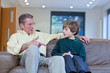Grandfather talking to grandson on couch