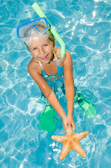 Snorkel girl with starfish in blue water