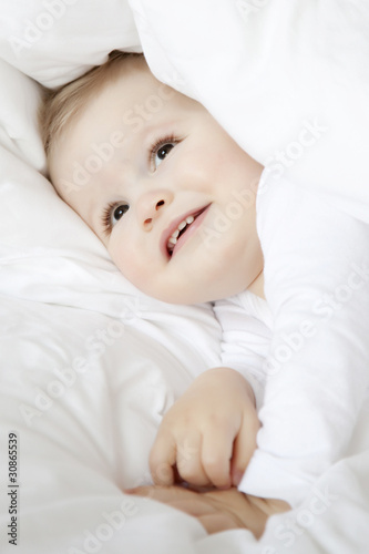 cute little boy hiding under duvet