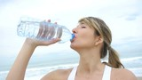 Portrait of woman drinking water from bottle at the beach