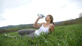 Portrait of woman drinking water from bottle in a green field