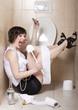 Leinwanddruck Bild - Drunk woman sitting dizzy on the toilet floor