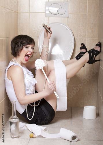 Leinwanddruck Bild Drunk woman sitting dizzy on the toilet floor