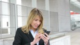 Businesswoman sending short message with mobile phone