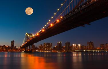 Moon rises over Manhattan Bridge at sunset. Ney York City